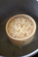 Bamboo steamer in a large pan