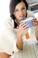 Young woman drinking white coffee from a bowl
