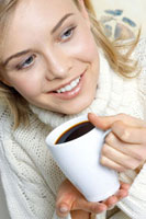 Young woman holding mug of hot drink in her hand