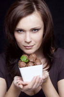 Young woman holding a bowl of chocolates
