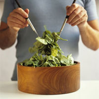 Man tossing a spinach salad