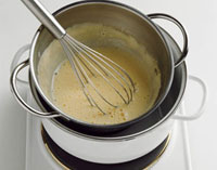 Whisking sauce in bain-marie with whisk