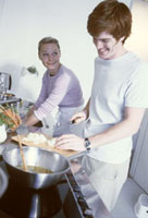 Young couple in kitchen cutting onions and washing up