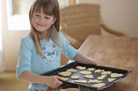 Girl holding a baking tray of biscuits