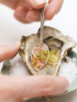 Hand sprinkling fresh oyster with sauce