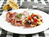 Plate of appetisers: sausage,ham and vegetable salad
