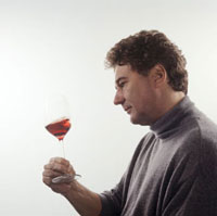 Swirling glass of wine: oxygenating,checking consistency