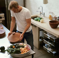 Man preparing vegetable tajine in a kitchen