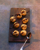 Profiteroles with chocolate icing on wooden board