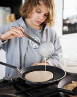 Boy putting pancake mixture into frying pan