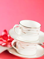 Two stacked teacups and saucers against pink background