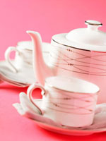 Teapot and two teacups and saucers