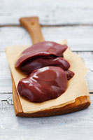 Turkey liver on paper on wooden board