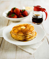 Pancakes with butter and maple syrup,strawberries (USA)