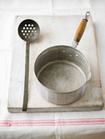 Saucepan and slotted spoon on a wooden board