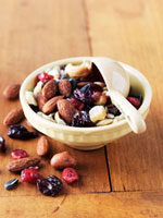 Snack Mix; Nuts and Dried Fruit in a Bowl with Measuring Cup