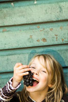 Little girl eating grapes