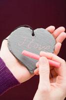 Hand writing I love you in chalk on a slate heart