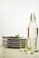Cutlery,pile of plates,bottle of water and glasses