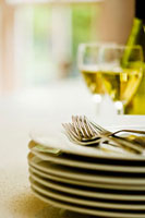 Pile of plates,cutlery and glasses of white wine