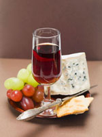 Blue cheese,crackers,grapes,glass of red wine on plate