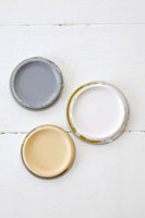 Lids from three different pots of paint on wooden background