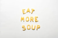 The words EAT MORE SOUP in alphabet pasta