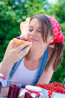 Young woman eating bread roll with jam