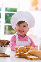 Little girl in chef�fs hat sitting at table with muffins
