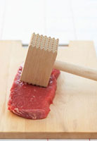 Beef with meat mallet on chopping board