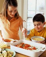 Girl and boy making vegetable lasagne together