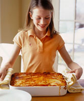 Girl holding vegetable lasagne in baking dish