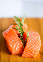 Fresh salmon with rosemary on a wooden board