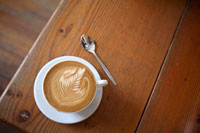 Coffee with milk foam on wooden table