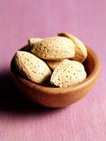 Several almonds in wooden bowl