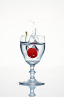 Cherry falling into a glass of cherry schnapps