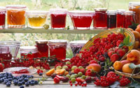 Jars of different jam and fresh fruit in front of window