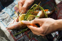 Hands holding smoked bass stuffed with lemon�Cthyme and ros