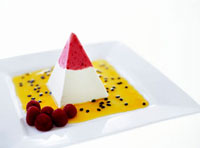 Ice cream pyramid with passion fruit sauce and raspberries
