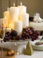 Christmas table decoration with candles,grapes and figs