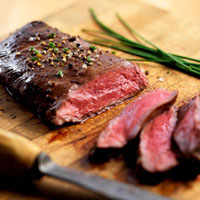 Partially Sliced Rare Flank Steak on Cutting Board