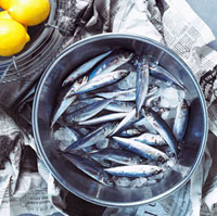 Bowl of Fresh Sardines on Newspaper with Lemons