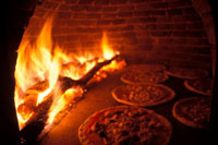 Pizzas in pizza oven with wood fire
