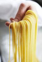 Hand holding fresh,home-made spaghetti
