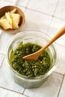 Pesto in jar with wooden spoon