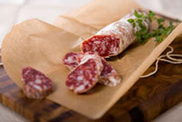 Partially Sliced Stick of Salami on Brown Paper; Cutting Boa