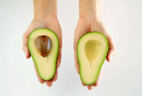 Hands holding two avocado halves