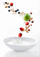 Cereal,fruit and nuts falling into bowl of milk
