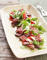 Peppered beef fillet with red peppers and salad leaves