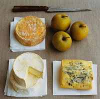 Three French cheeses on paper with apples